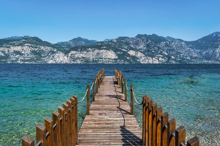 Wooden dock jutting out into the turquosie water of Lake Garda