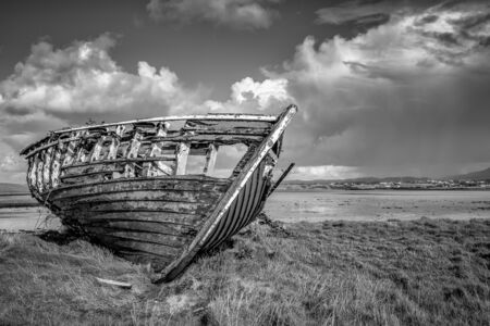 An old wooden Fishing boat decaying on a beach in Donegal Ireland