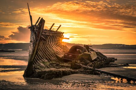 Old ship wreck called Bad Eddie. This was taken at low tide at sunset in Donegal Ireland Stock Photo
