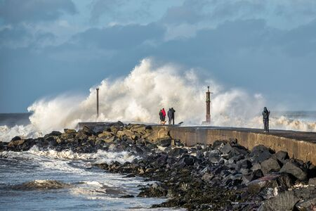 Ocean waves crashing on the end of the Barmouth in Castlerock, Norther Ireland