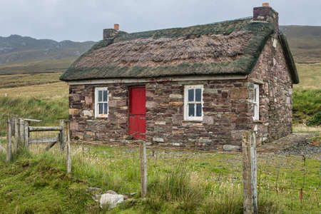 Achill Island, Ireland- Jul 31, 2020: A small traditional Irish thatched cottage.