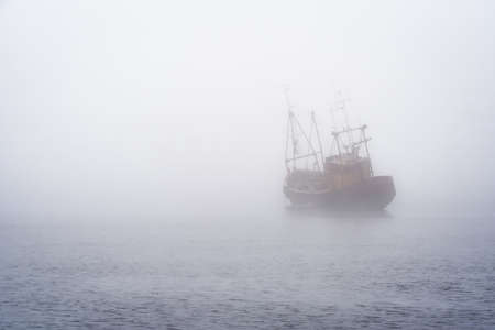 A small fishing boat anchored in think fog in Ireland