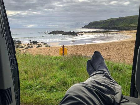 Relaxing in a camper van on a beach in Ireland Stock fotó