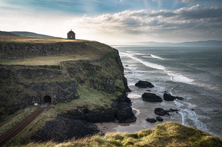 Railway line running along the Causway Coast in Northern Ireland. A tunnel goes under the Musseden Temple