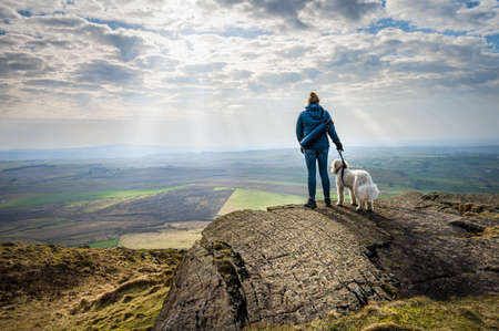 A women and her white dog enjoying the view of the Irish countryside after climbing Slemish Mountain in Northern Ireland Stock fotó