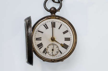 Antique pocket watch with roman numerals and the front glass open,  on a white background