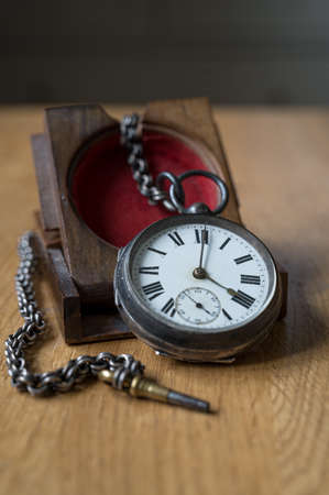 Antique pocket watch with roman numerals, and a metal chain on a wooden stand Stock fotó