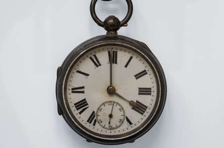 Antique pocket watch with roman numerals on a white background