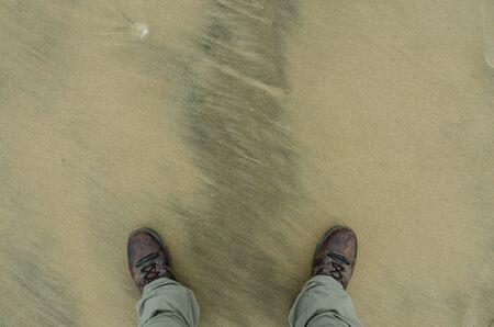 naar beneden kijken: Een neerkijken op laarzen op een vloer schuren Stockfoto
