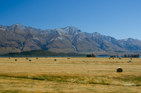 Straw haystacks on the field after harvest, with a lake and mountains at the background Standard-Bild