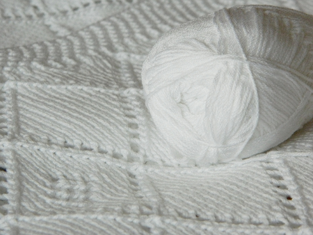 purl: White knitted blanket and a skein