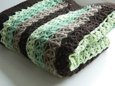 Multicolored crocheted pattern. Green, light green, brown, beige. Stock Photo