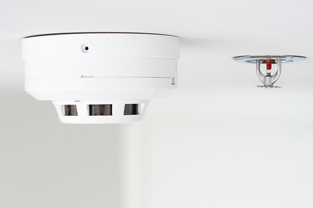sprinkler alarm: smoke detector and pendent fire sprinkler on a ceiling