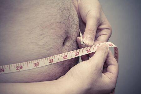 fat man measuring his waist, for diet