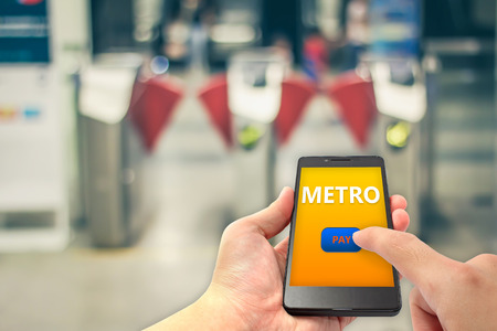 hand hold smartphone and finger touch on pay button for metro fare payment with blur metro gate background