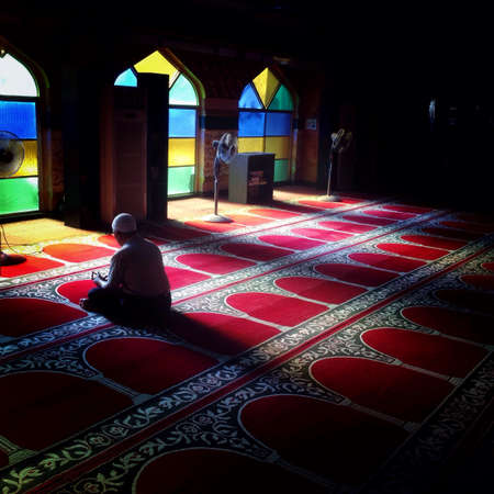 man: Man praying in mosque