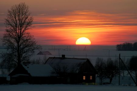 Rural house in the winter evening in beams of the coming sun Stock Photo - 2505237