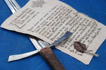 indulgence: The ancient indulgence and the sword laying on a dark blue canvas