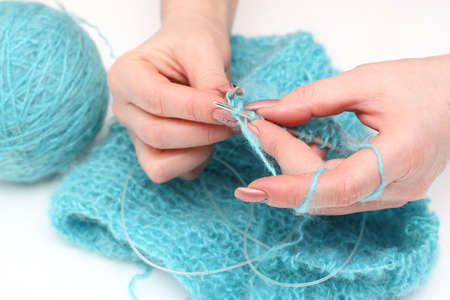 woman hands knitting a turquoise pullover photo