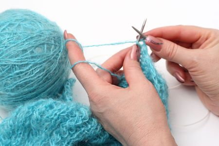 woman hands knitting a turquoise pullover