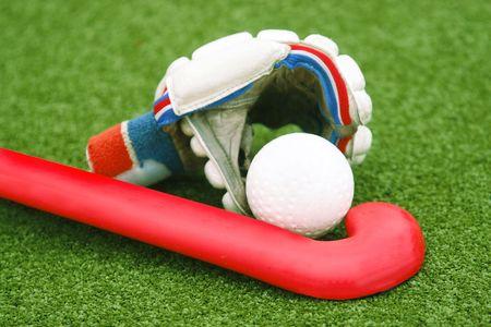 hockey cesped: Guante con un palo de color rojo sobre la hierba verde  Foto de archivo