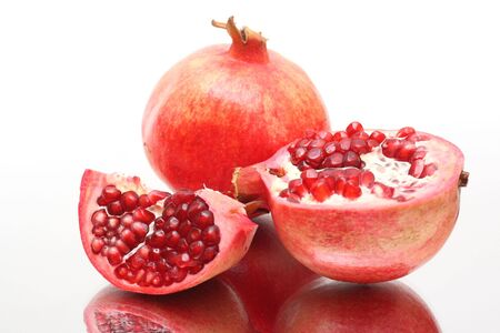 Fresh appetizing pomegranates on white background photo