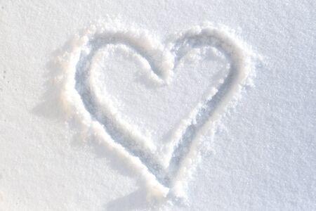 Heart drawn on white-blue snow photo