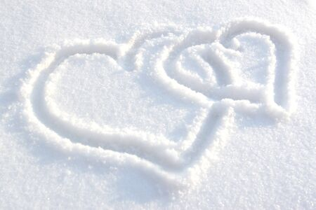 Two heart drawn on white-blue snow photo