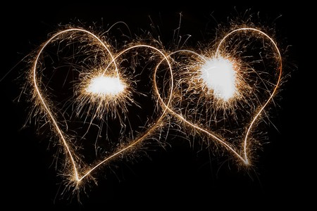 Two sparkling hearts isolated on black photo