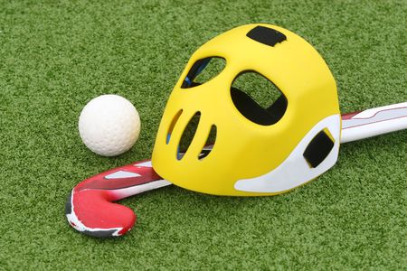 Field hockey equipment on green grass Stock Photo