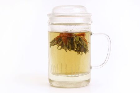 Herbal tea with blooming tea flower in glass cup photo