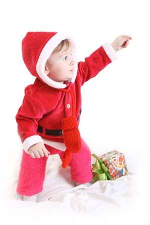 Little happy girl in red santas clothes with present isolated on white photo