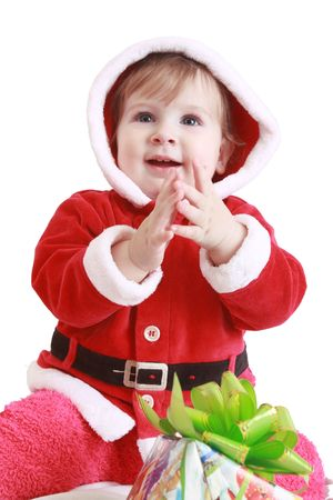 Little happy girl in red santas clothes clapping isolated on white photo
