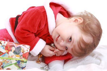 Little happy girl in red santas clothes with present isolated on white