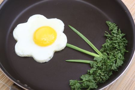 Flower shaped fried egg with parsley and spring onions photo