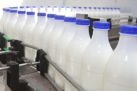 White milk bottles with blue cover at conveyor