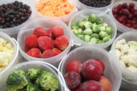 Frozen summer fruits and healthy vegetables in plastic containers photo
