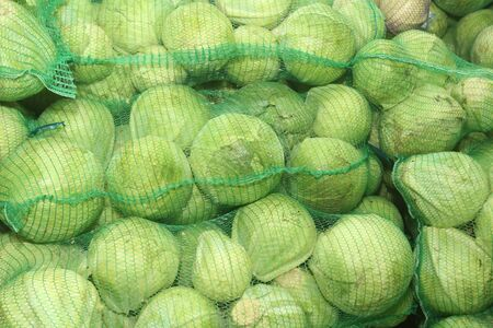 Heads of cabbage in the netting for sale