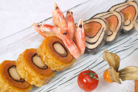 Stuffed fish and prawns with vegetables on plate Stock Photo