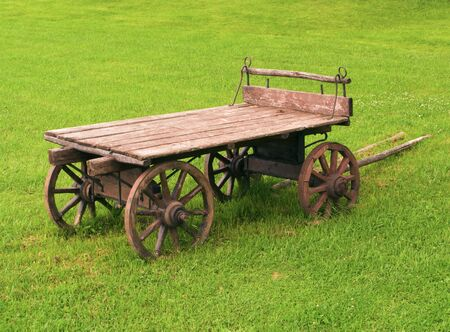 old-fashioned wooden cart in a green grass field, Russia farm photo