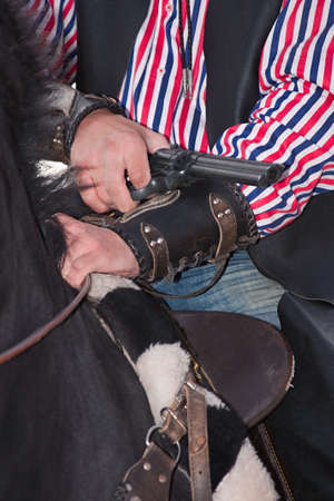 Revolver in arm of a cowboy sitting a horse photo