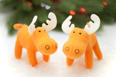 Two toy elks in artificial snow with pine on background photo