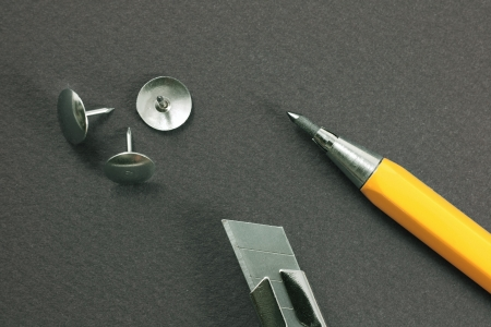 drawingpin: Retractable blade knife, mechanical pencil, drawing-pin on a gray cardboard