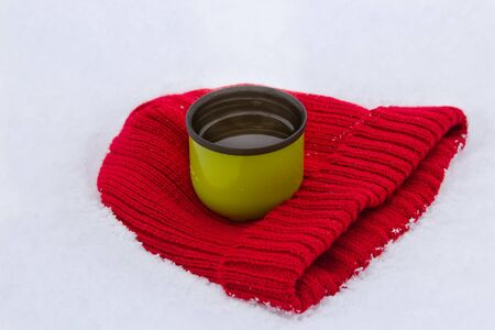 warm drink: Red wool hat and green mug with warm drink