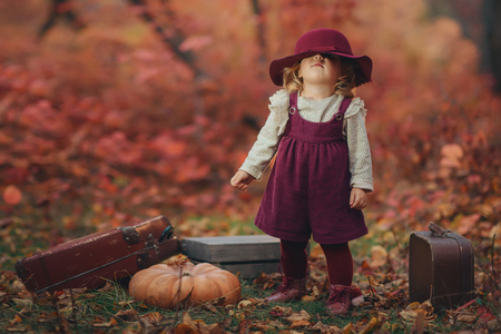 a little cute girl in a claret hat and dress of ancient suitcase in hands stands expectant in the autumn forest on a background red leaves and trees