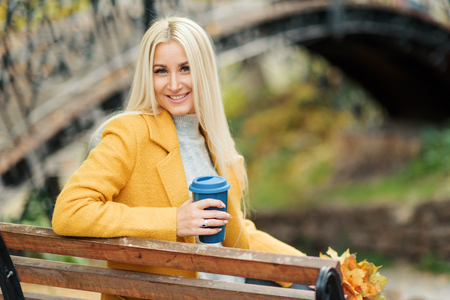 Young stylish blond woman drinking coffee to go in a autumn park. Outdoor