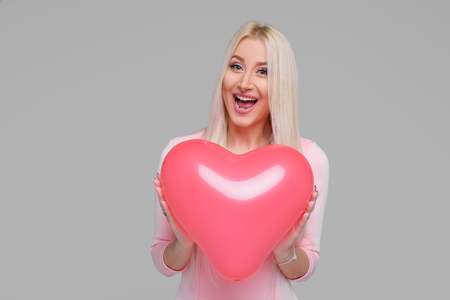 Beautiful young blond woman with pink heart shape air balloon on grey background. Woman on Valentine Day. Symbol of love. Space for text Standard-Bild