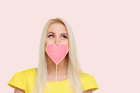Valentine Day. Beauty young blond model girl with Valentine red heart on pink background. Copy space for text