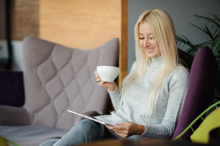 Reading Concept. Young blond Woman using Tablet and Drinking Coffee. Relaxing in Cozy cafe, Sit on the Chair