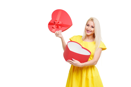 Blond girl in yellow dress with heart shape box for Valentine Day Holiday on white isolated background. Copy space for text